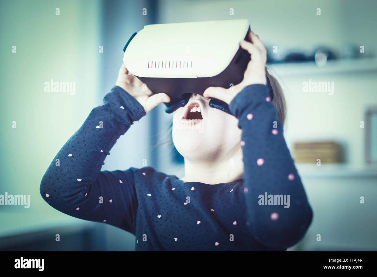 Excited amazed little girl experience looking in VR glasses goggles. - Stock Image