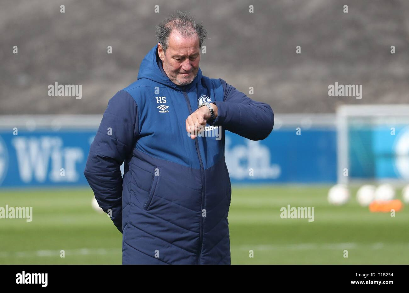firo: 25.03.2019, Football, 2018/2019, 1.Bundesliga: FC Schalke 04 - Training Huub Stevens, gesture, looks at the clock   usage worldwide - Stock Image
