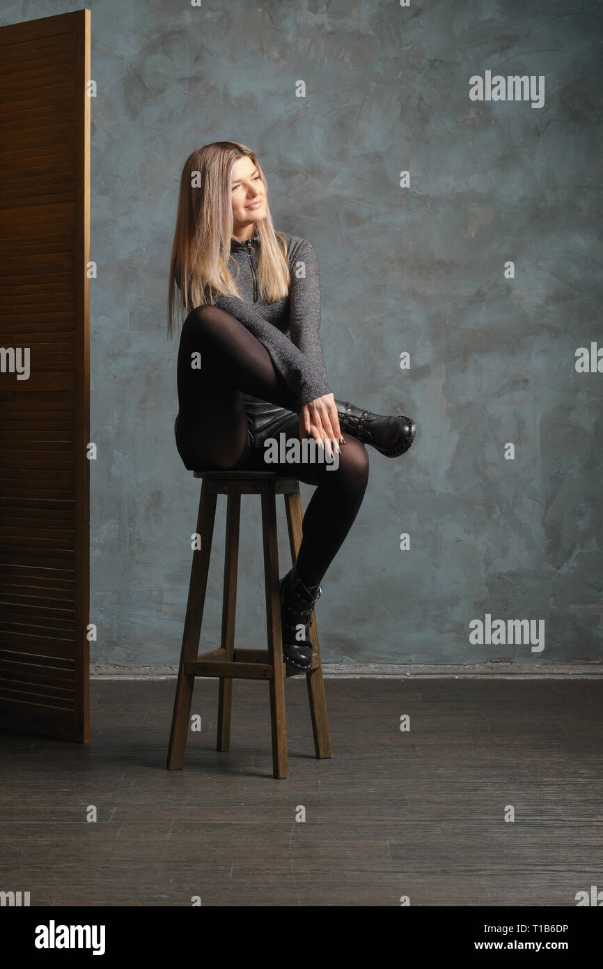Cute girl in top, leather shorts and dense tights sitting on chair with crossed legs near folding screen Stock Photo