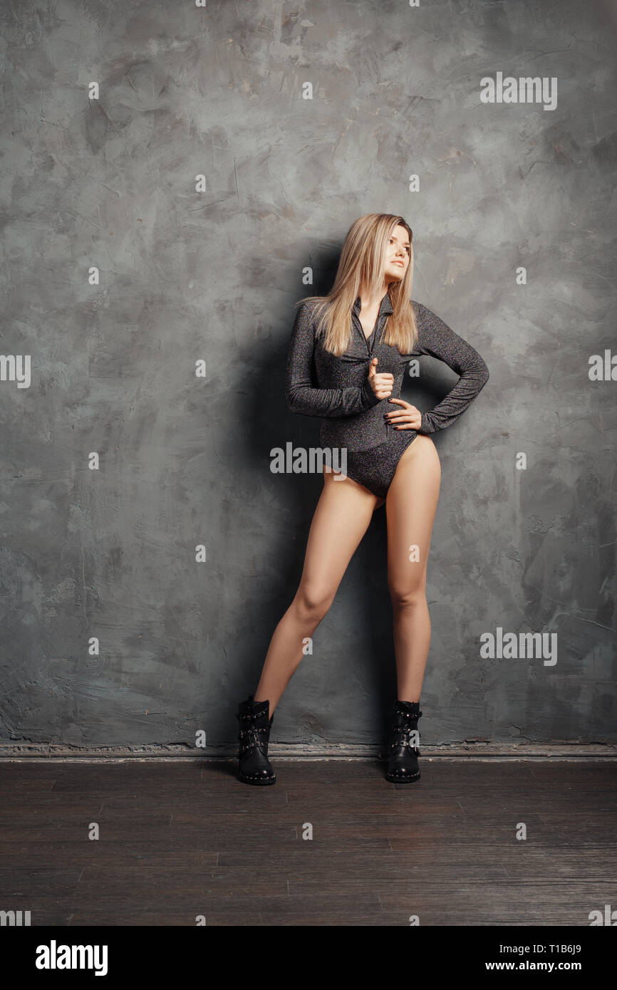 Pretty size plus model posing near folding screen over grunge abstract wall on background in closed body and rough boots - Stock Image