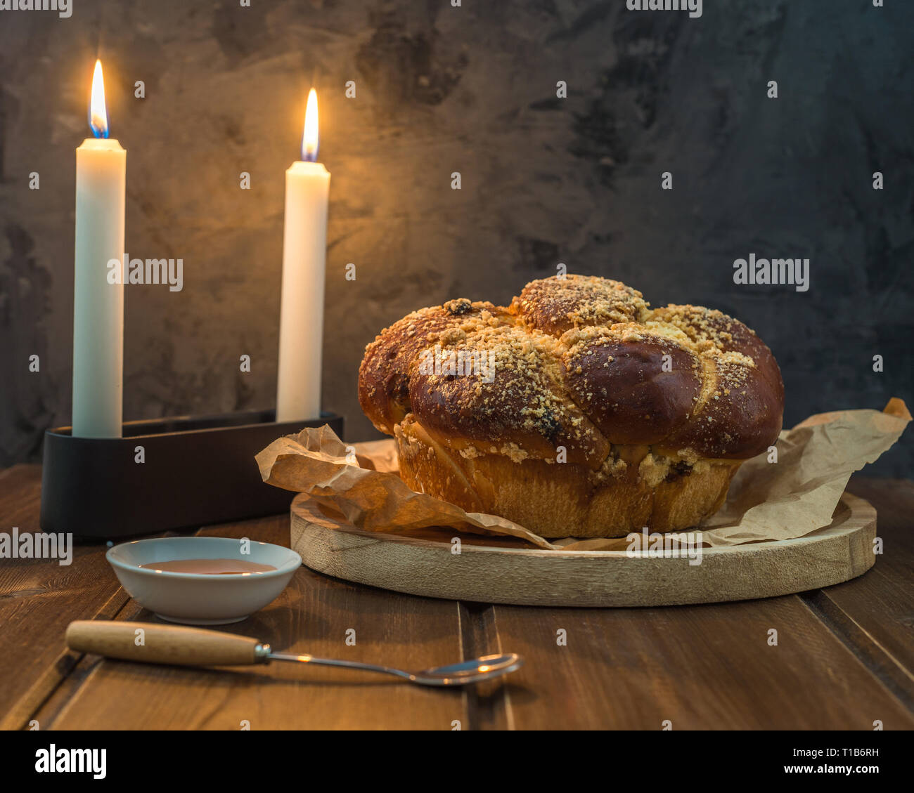 Sweet Challah bread on a wooded round plate on wooden brown table with honey and two candles on Shabbat evening making Kidush / black background with - Stock Image