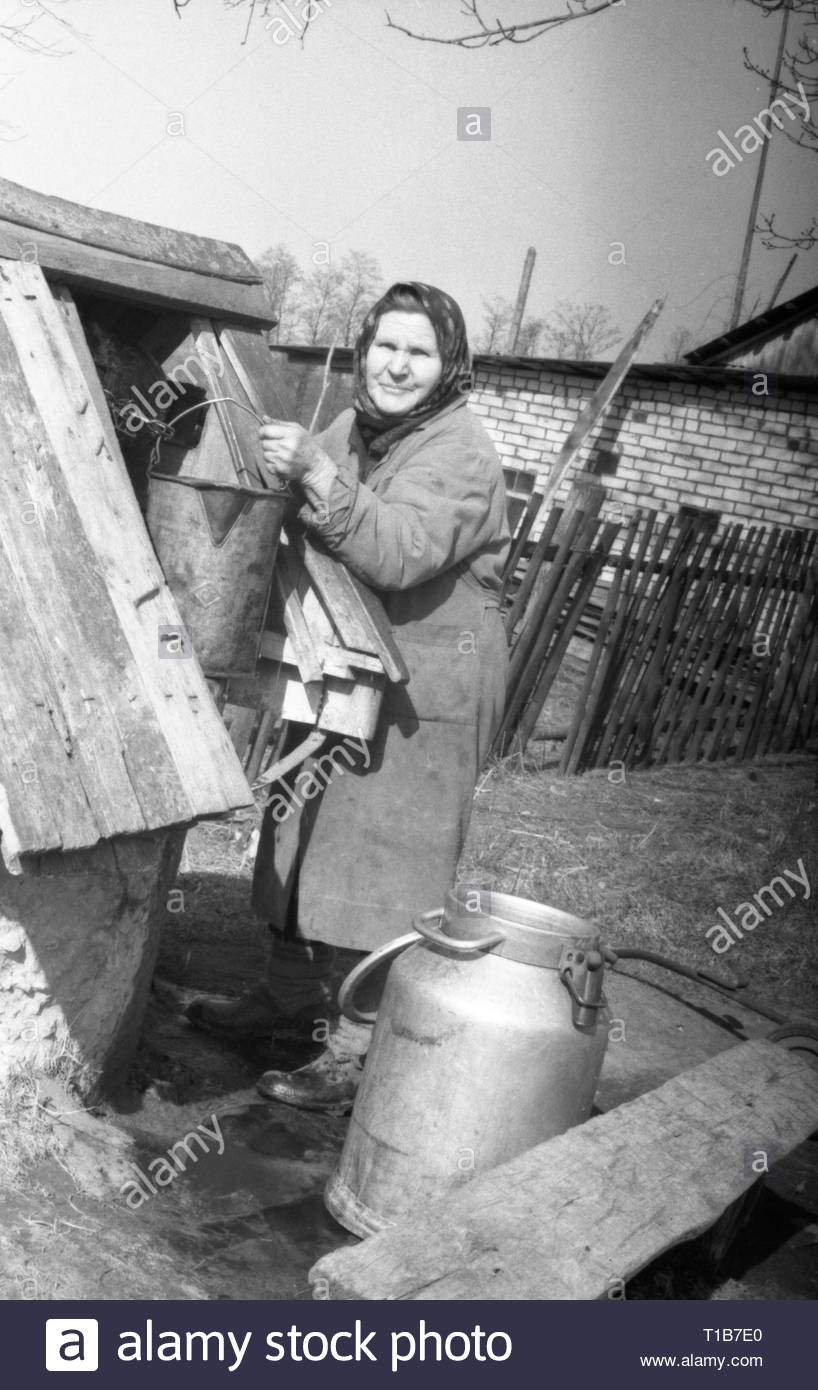 An elderly villager came with a large can to collect water from the well. The woman took out a bucket of water. Undoubtedly it is difficult for her, but no she can not help. She's single. - Stock Image