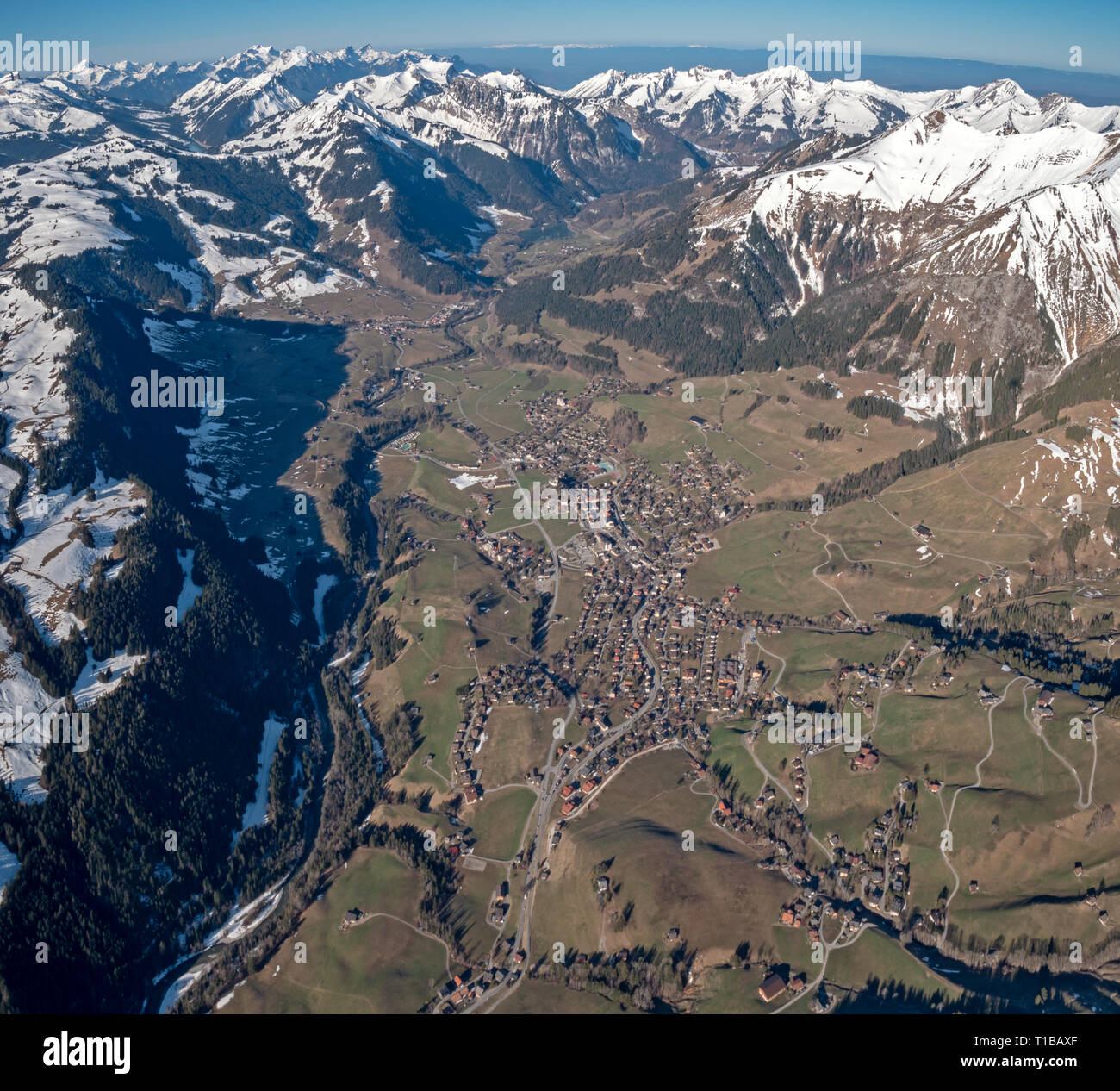 Stunning Aerial views over the a Swiss Alpine town and valley basin, surrounded by snow covered high mountain peaks and mountains. Stock Photo