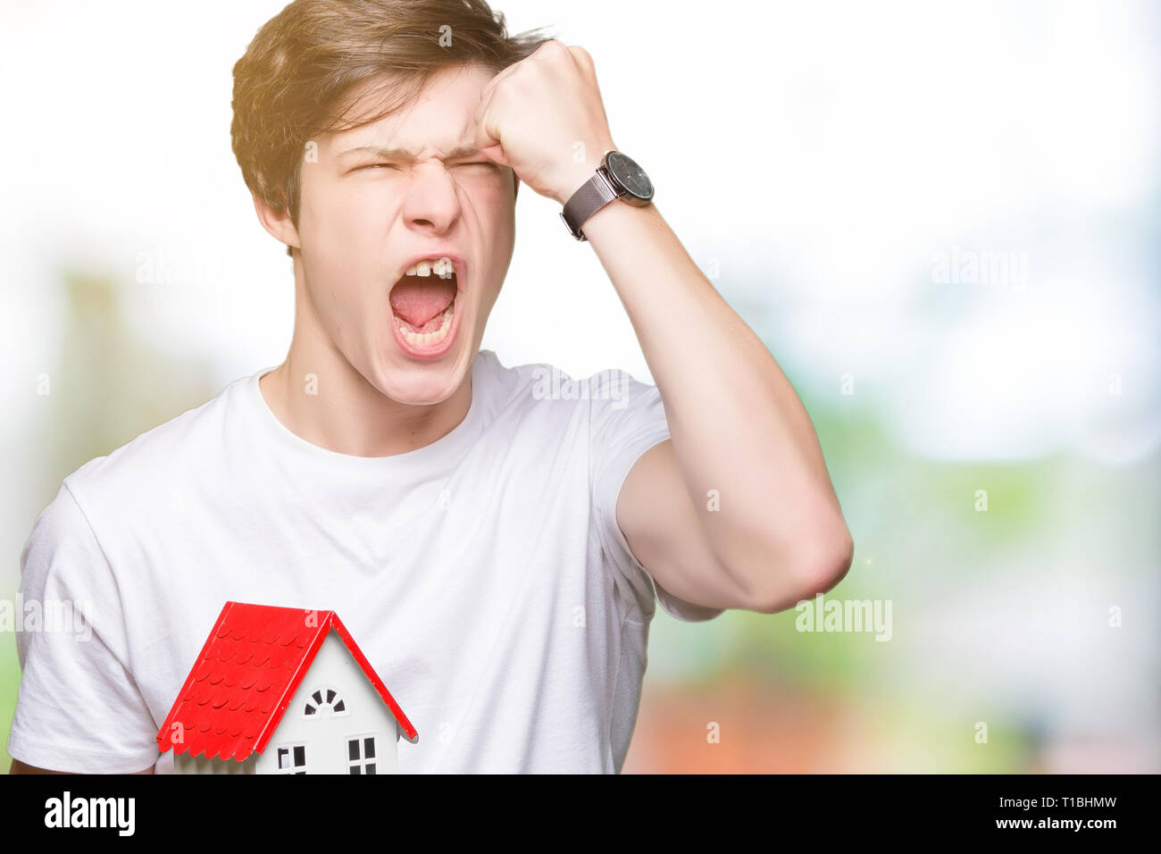 Young man holding house over isolated background annoyed and frustrated shouting with anger, crazy and yelling with raised hand, anger concept - Stock Image