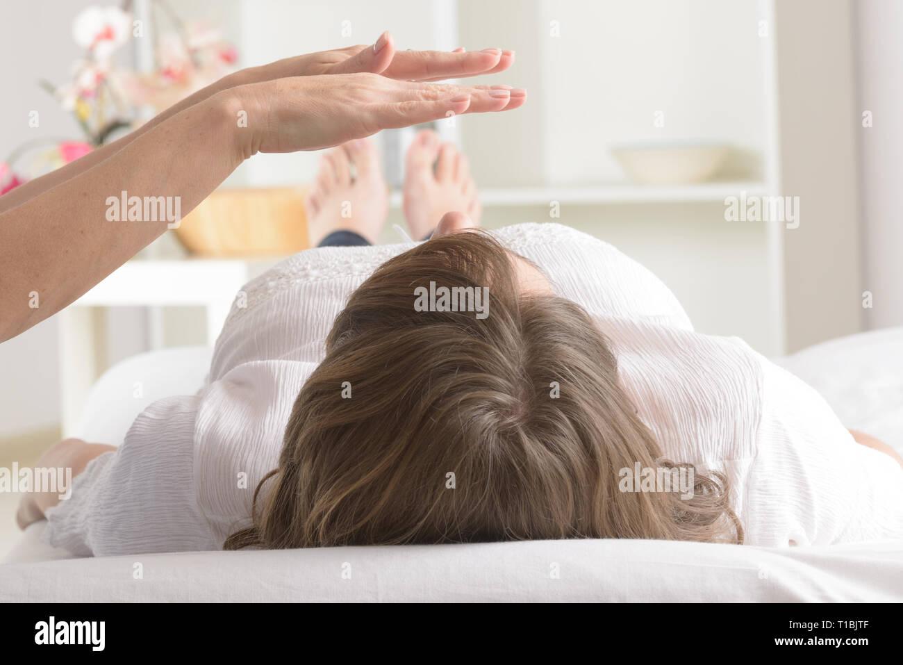 Professional Reiki healer doing reiki treatment to young woman - Stock Image