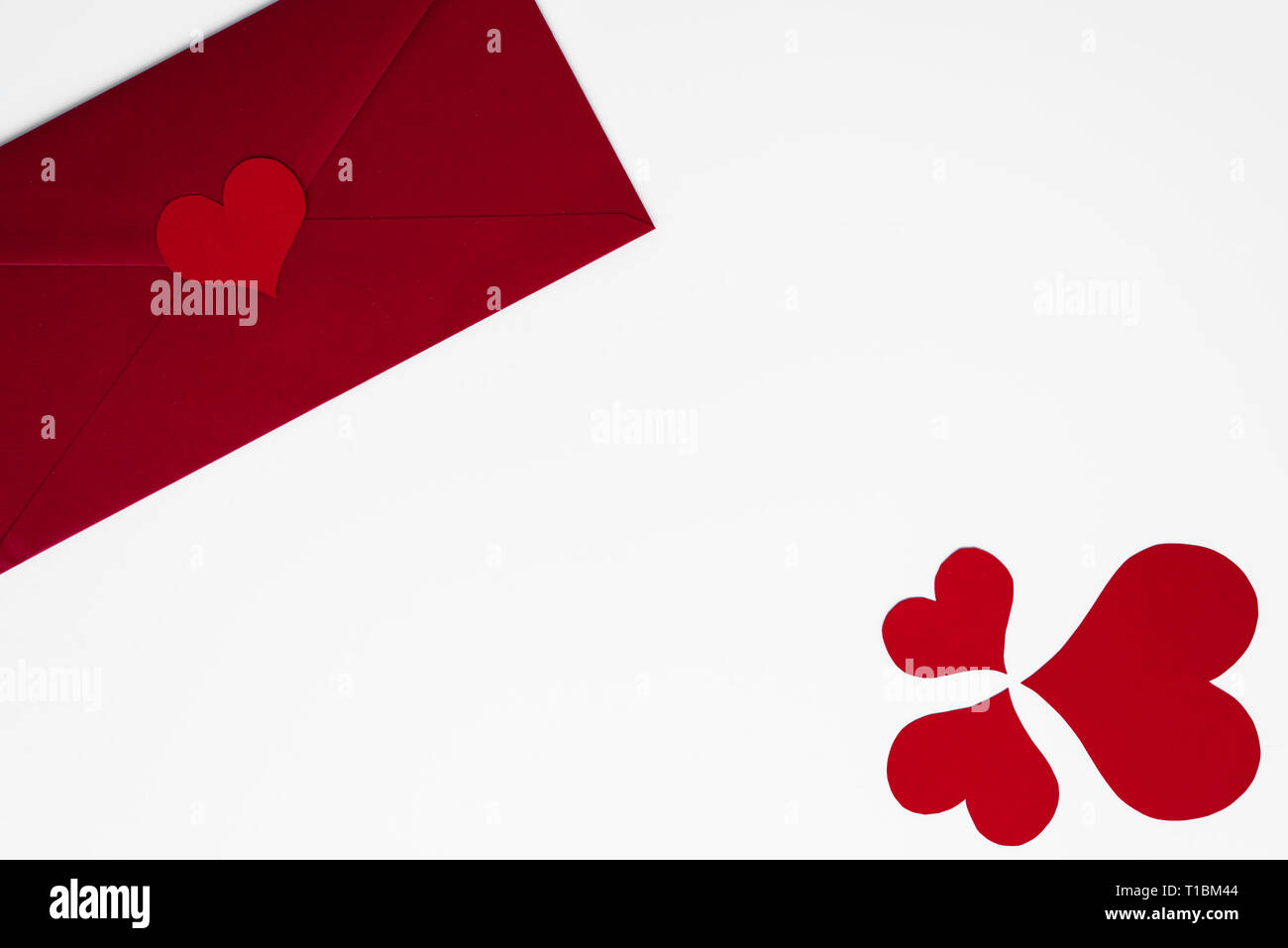 Love letter concept in red envelope. Romantic hearts arranged as clover for luck, on white background with copy space for Happy Valentines text. Mothe - Stock Image