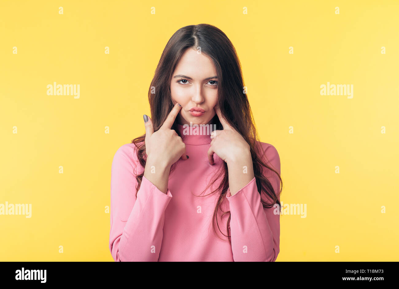 Displeased capricious woman grimacing isolated on yellow background - Stock Image