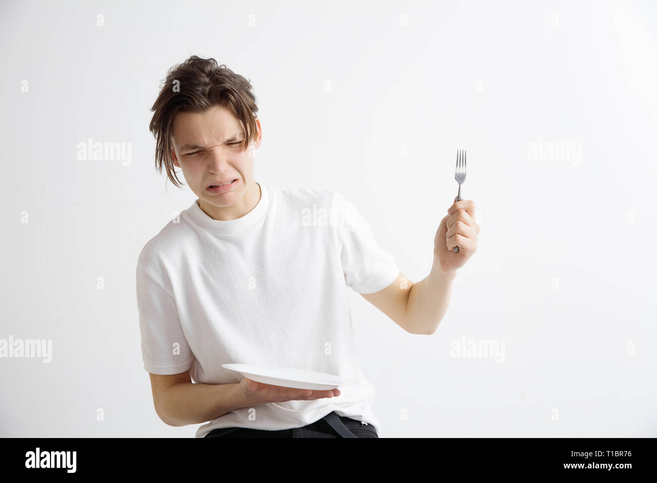 Young sad attractive caucasian guy holding empty dish and fork isolated on grey background. Copy space and mock up. Blank template background. Reject, rejection concept - Stock Image