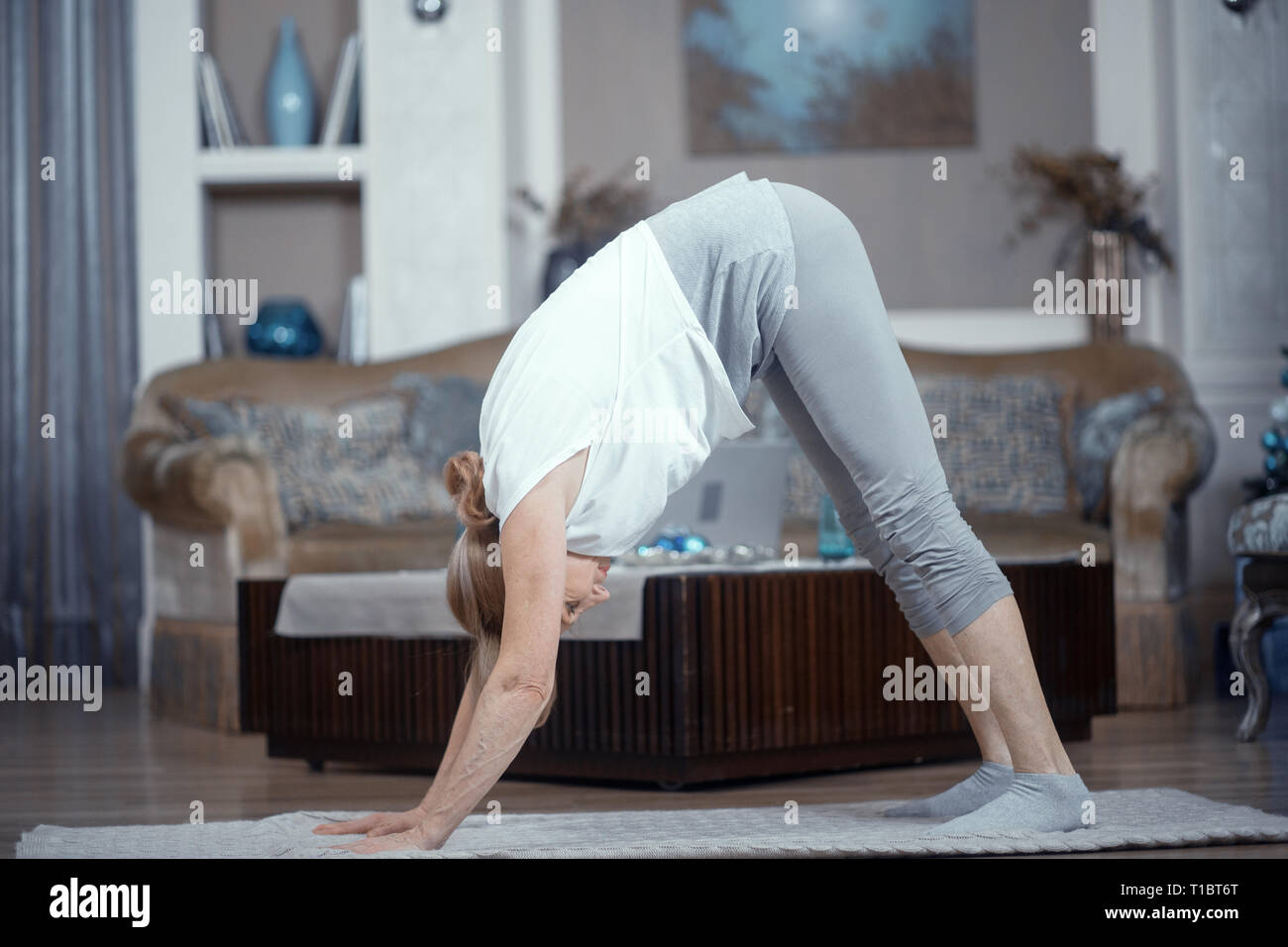Adult Woman Over 50 Years Old Doing Yoga At Home In The Living Room Stock Photo Alamy
