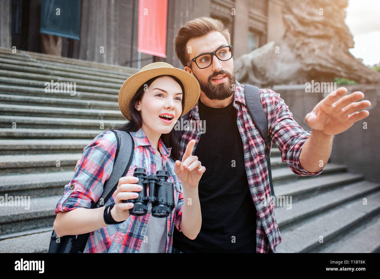 Amazed tourists stand in front of stairs. They point forward. Woman holds binoculars. They are in city. Bearded guy wears glasses. - Stock Image