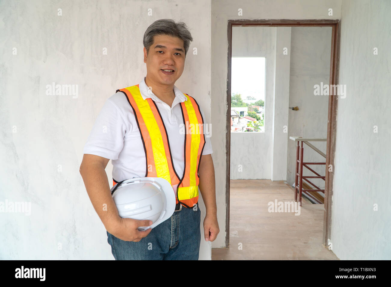 Asian professional engineer workering in house construction site for inspection of the cottage under construction Stock Photo