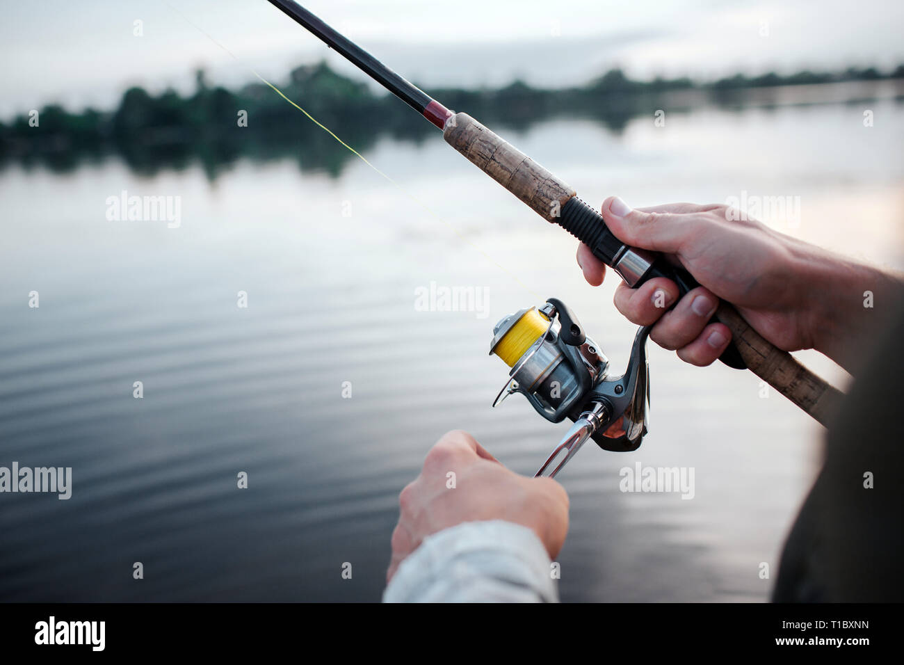 A picture of rotative spinner that guy holds in hands. He rotates reel with left hand. He is at lake. It is evening outside. - Stock Image