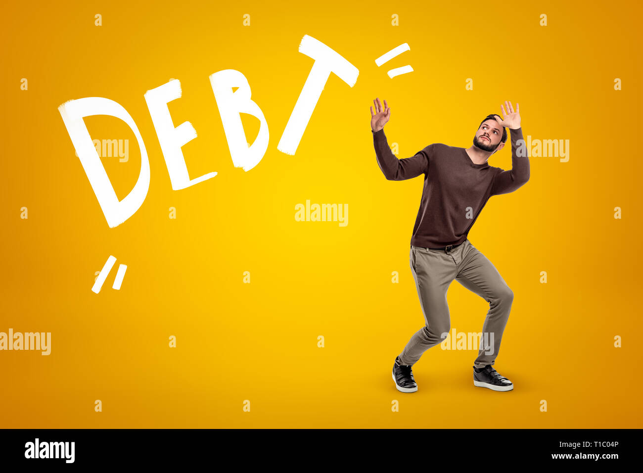 Young man wearing casual clothes protecting himself with hands from DEBT sign on yellow background - Stock Image