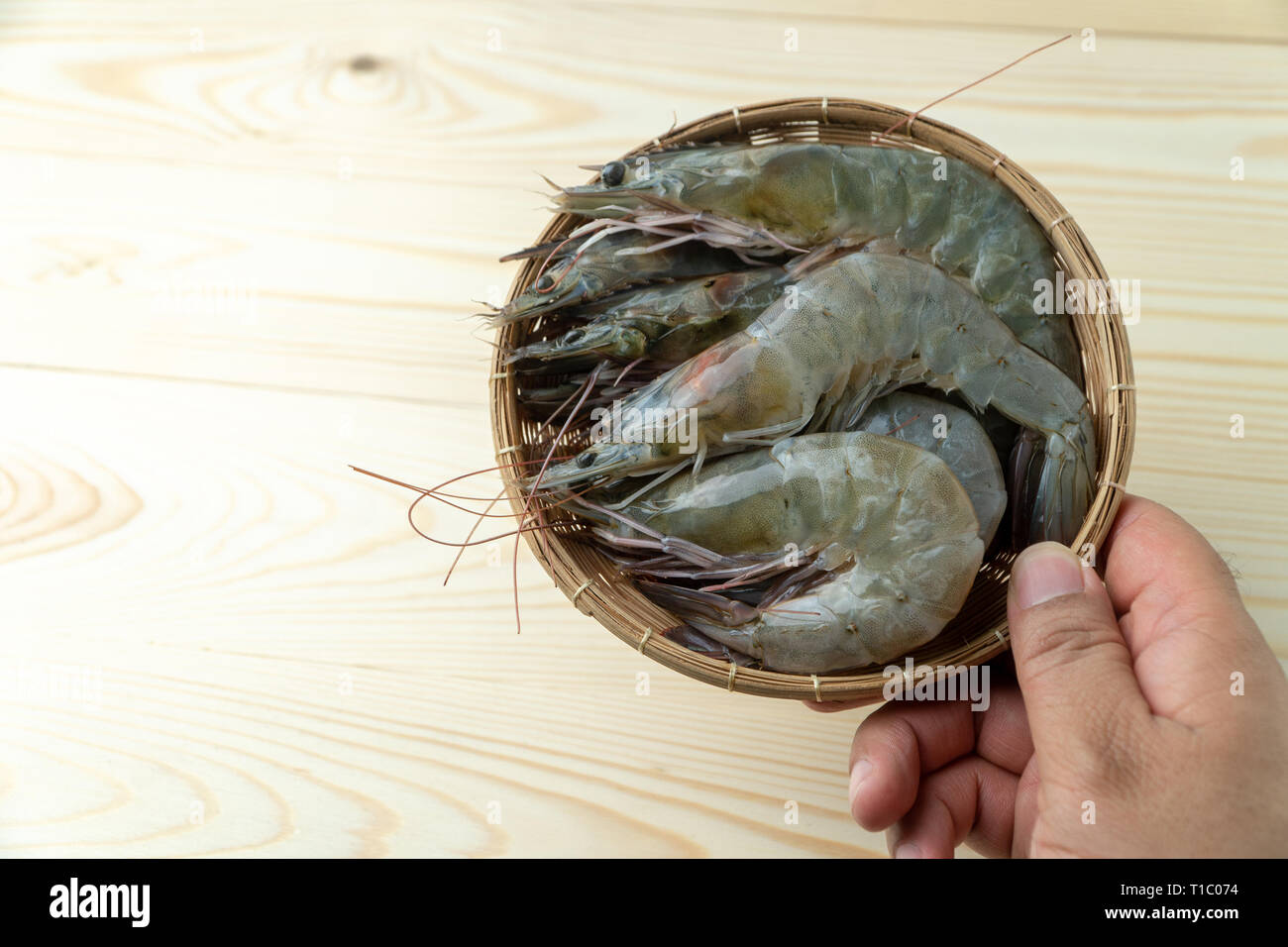 The Hands Of Men Are Holding Group Of Fresh Raw Pacific White Shrimp In Bamboo Bowl On Wooden Table T C on Caricature Woman Executives