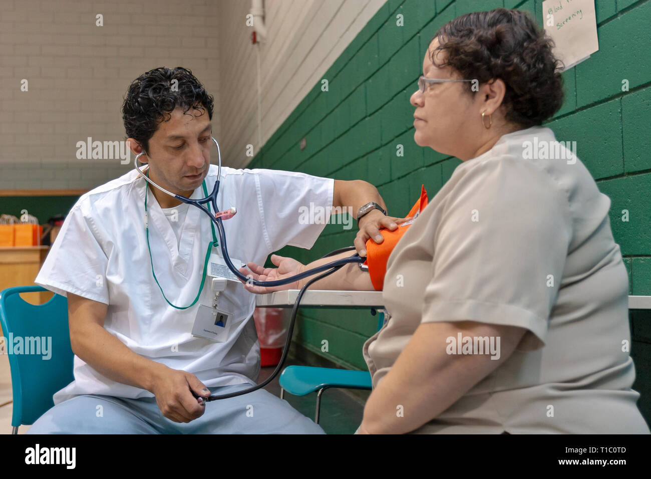 A male nurse takes the blood pressure of a middle-aged woman in a community outreach program. - Stock Image