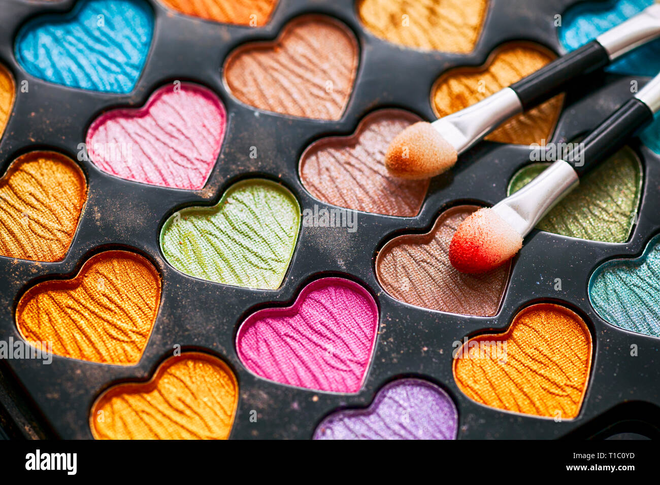 Eyeshadow heart shaped palette with two applicators. Close-up. - Stock Image