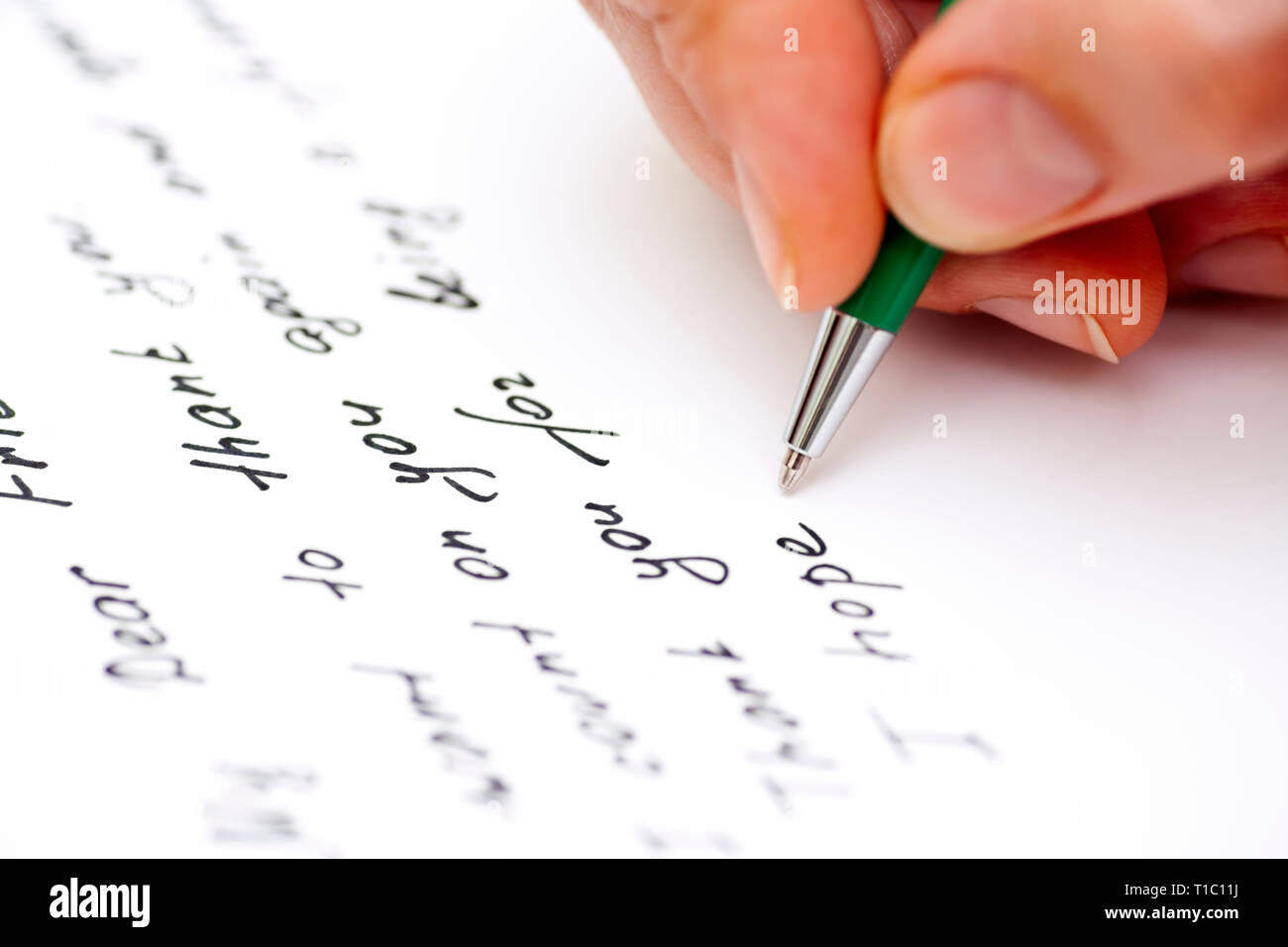 Woman hand with pen writing letter to the friend. Close-up. - Stock Image