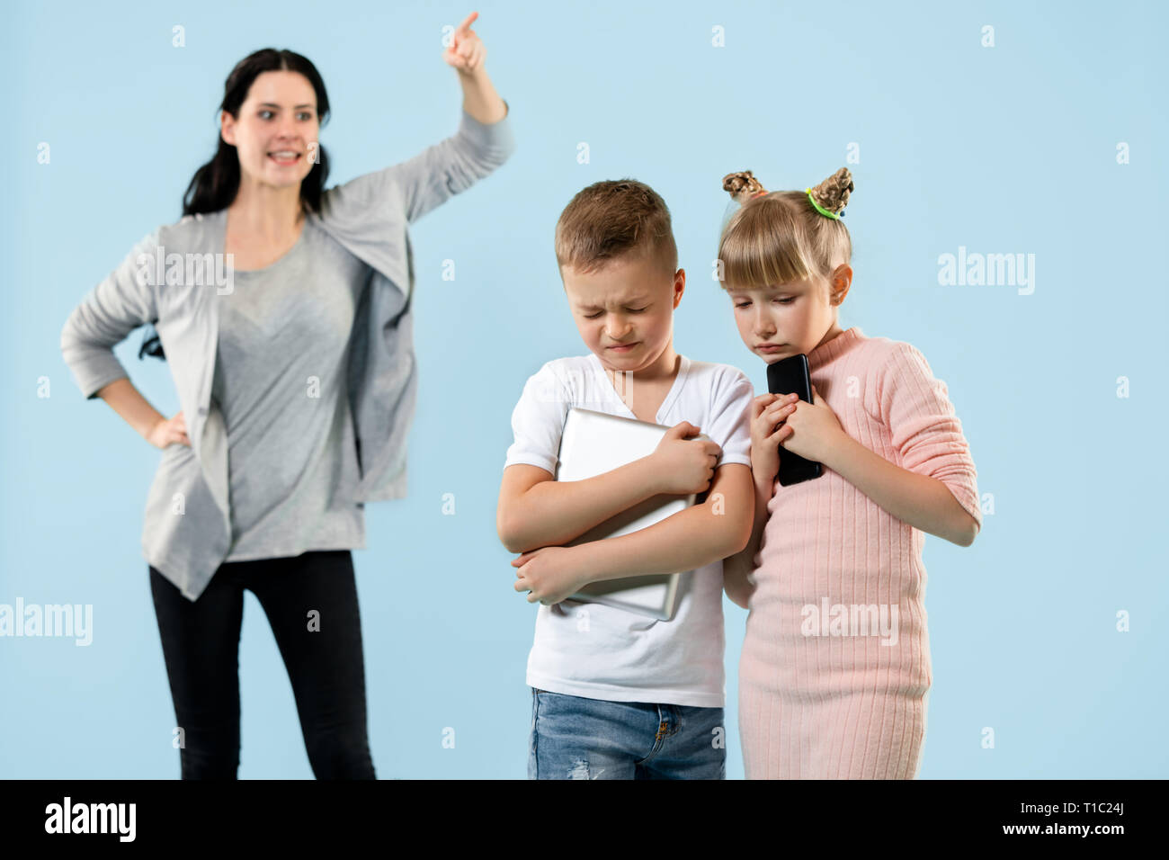 Angry mother scolding her son and daughter at home  Studio
