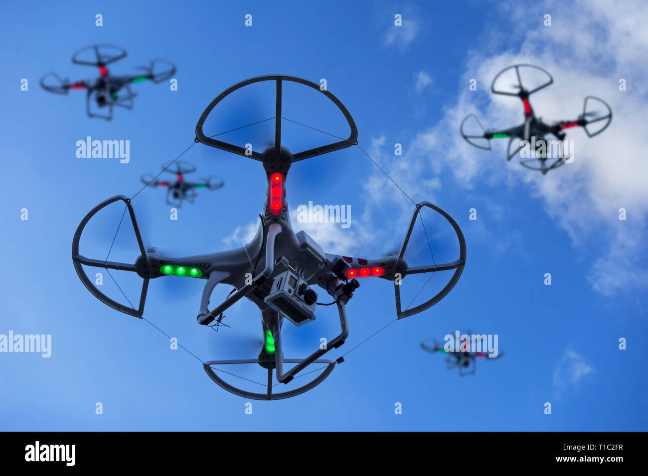 Group of miniature drones / unmanned aerial vehicles / UAV equipped with camera in flight against blue sky with clouds - Stock Image