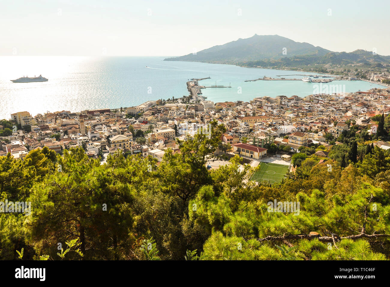 Beautiful and colorful landscape of Zakynthos in Greece. View on harbor, boats at sea and resort, with hill in the background. Zante Island. - Stock Image