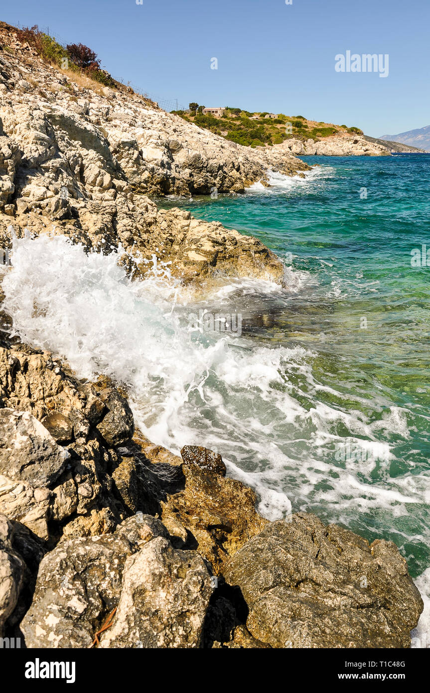 Phenomenal and scenic sea waves crashing against the rocky coast. Another sunny day during summer vacation in Greece, with view from seashore on blue, Stock Photo