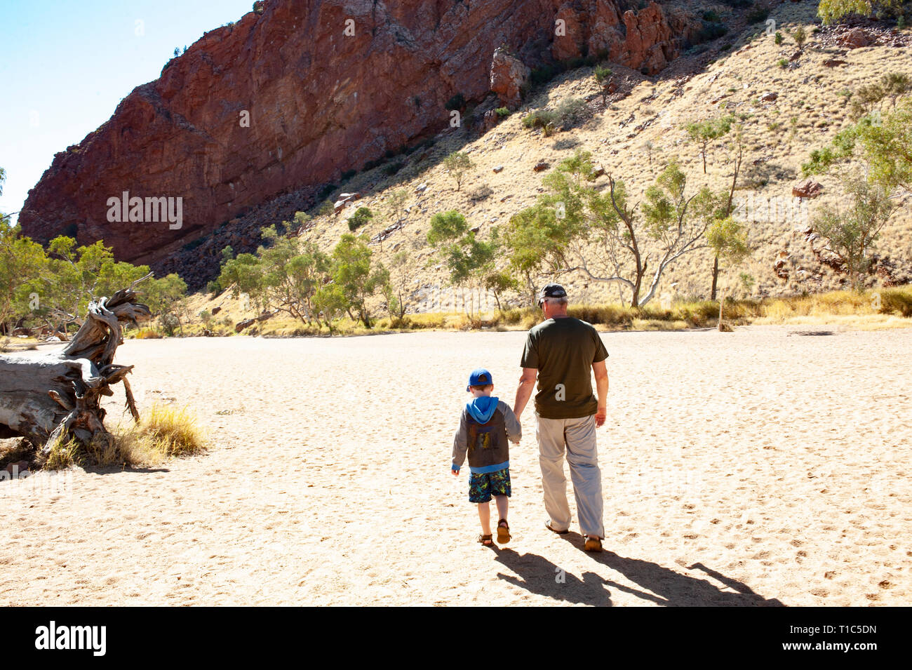 A father and son holding hands walking through Simpsons Gap, Northern Territory, Australia - Stock Image