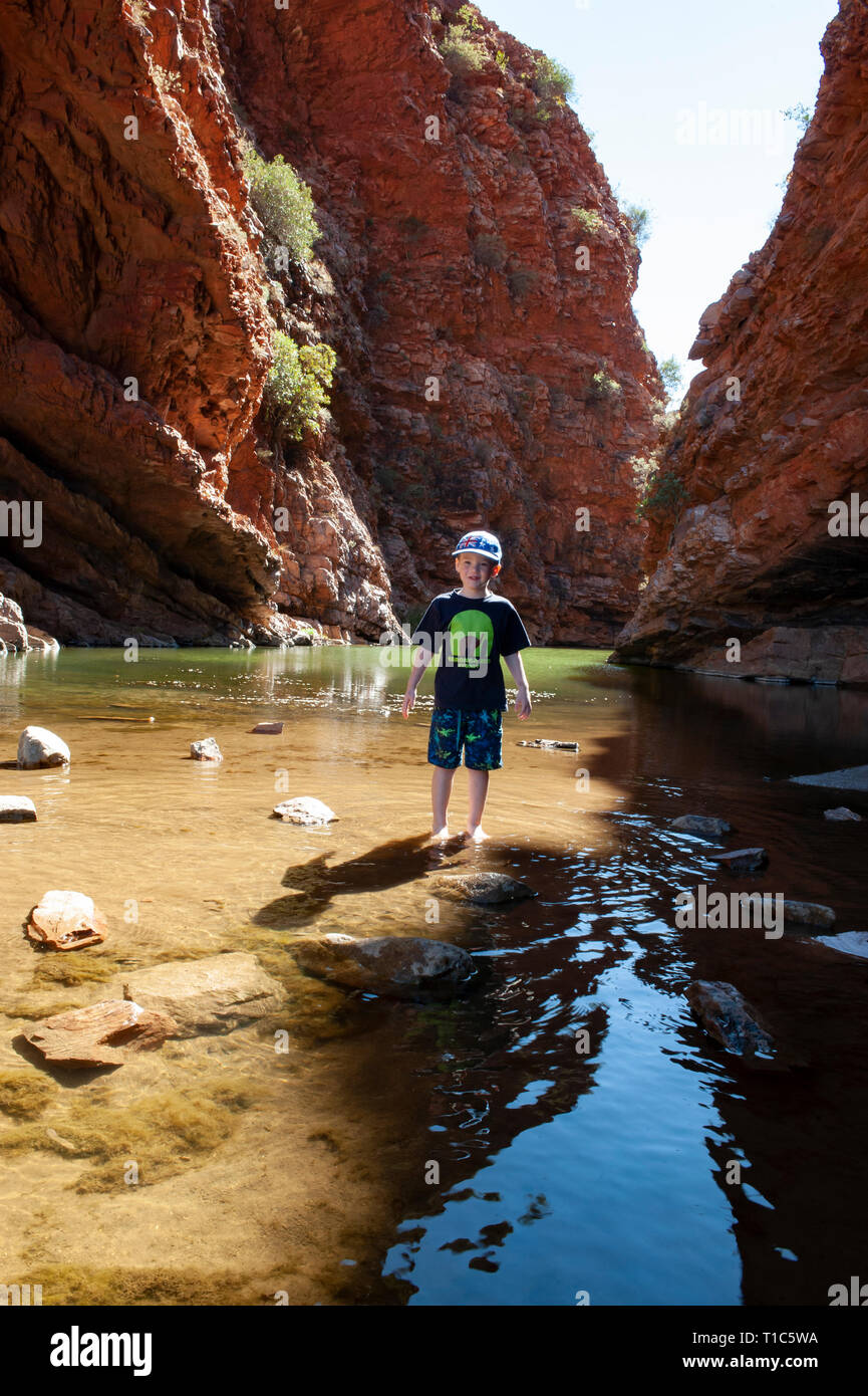 A 6 year old boy plays on the stepping stones in the shallow waters of Simpsons Gap, Northern Territory, Australia - Stock Image
