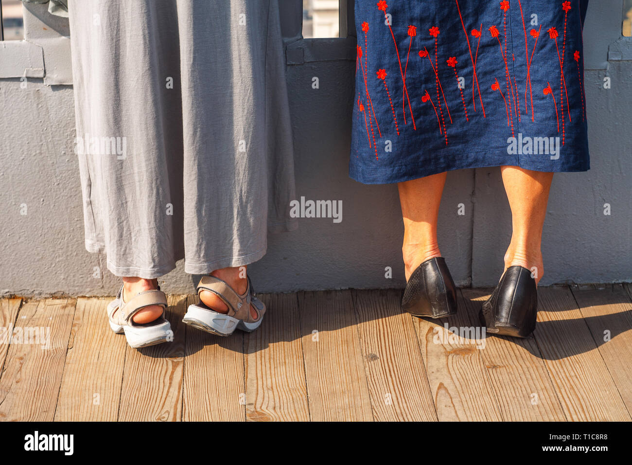 Two Adult Women in Long Skirts Standing on Tiptoes. Curiosity Peeping Concept. - Stock Image