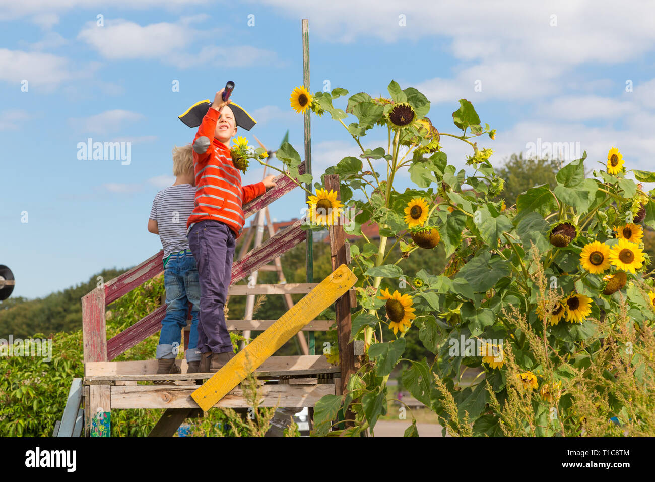 Kids playing pirates in urban gardens at Tempelhofer field, once airport, now a public park in Berlin, Germany - Stock Image