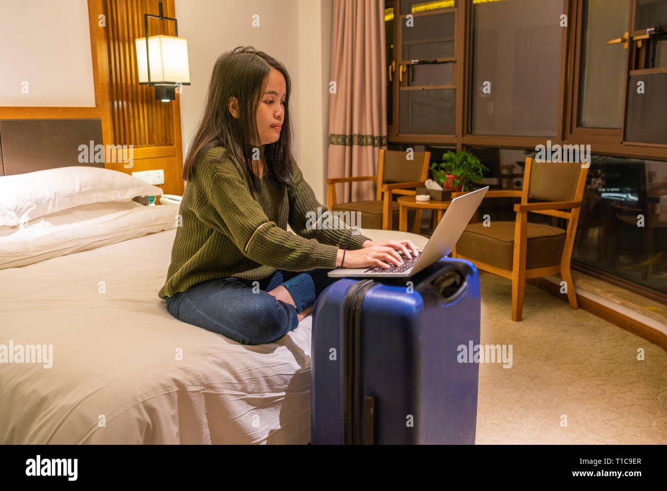 Asian businesswoman working on laptop in hotel room - Stock Image
