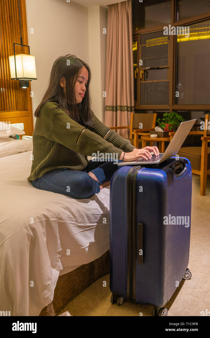 Asian woman working late on laptop at night - Stock Image