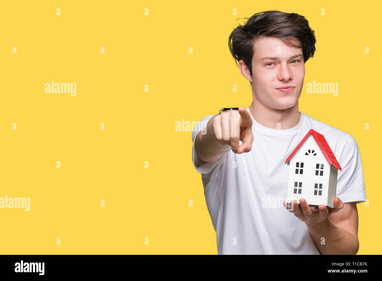 Young man holding house over isolated background pointing with finger to the camera and to you, hand sign, positive and confident gesture from the fro - Stock Image