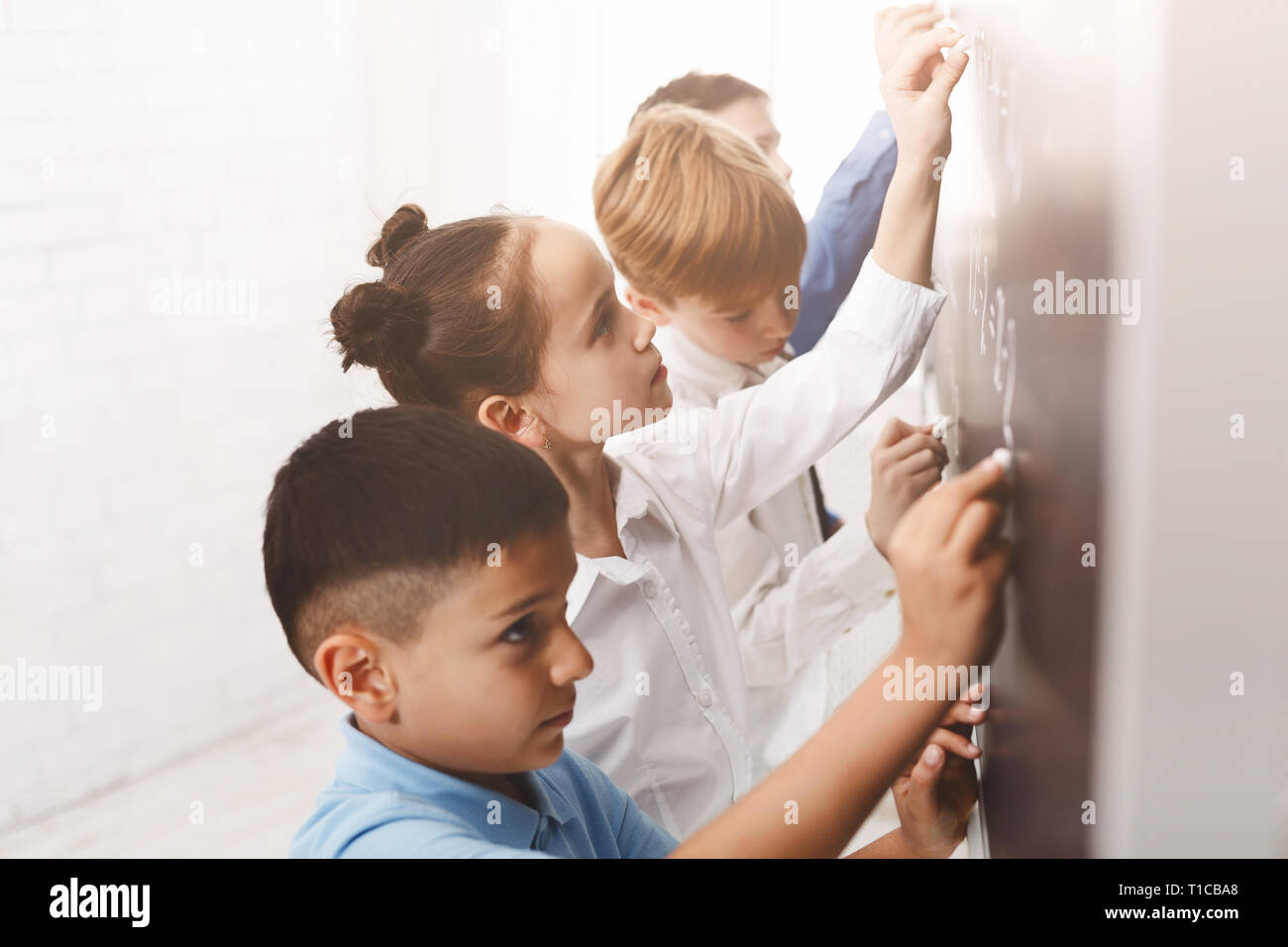 Children writing maths equations on the board - Stock Image
