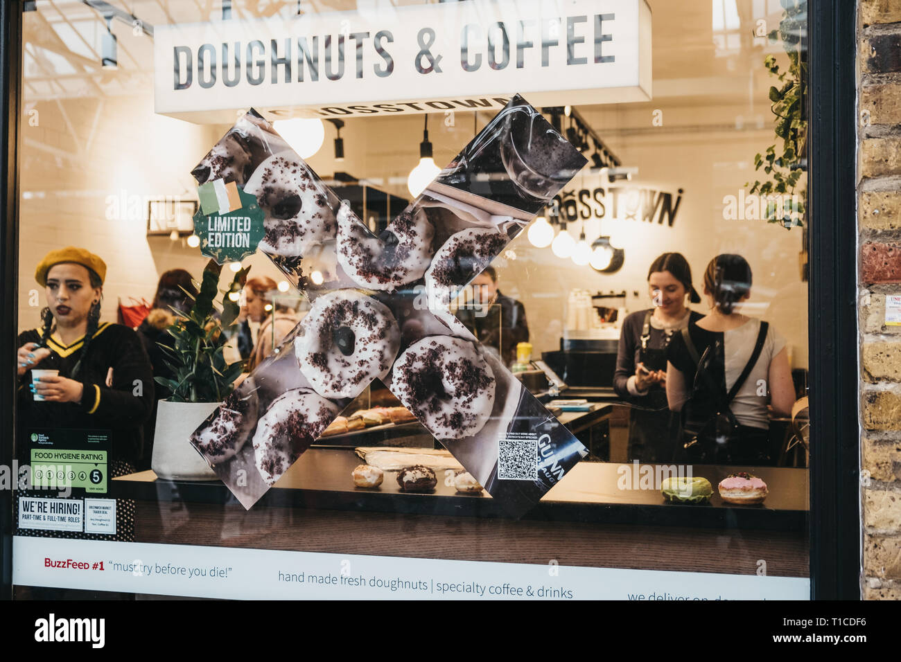 London, UK - March 16, 2019: View through the window of people inside Crosstown doughnuts and coffee cafe in Greenwich Market, the only market in Lond - Stock Image