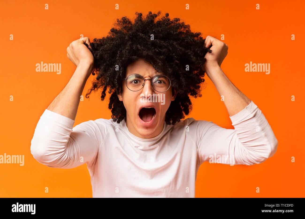 Emotional black man in despair pulling out his hair - Stock Image