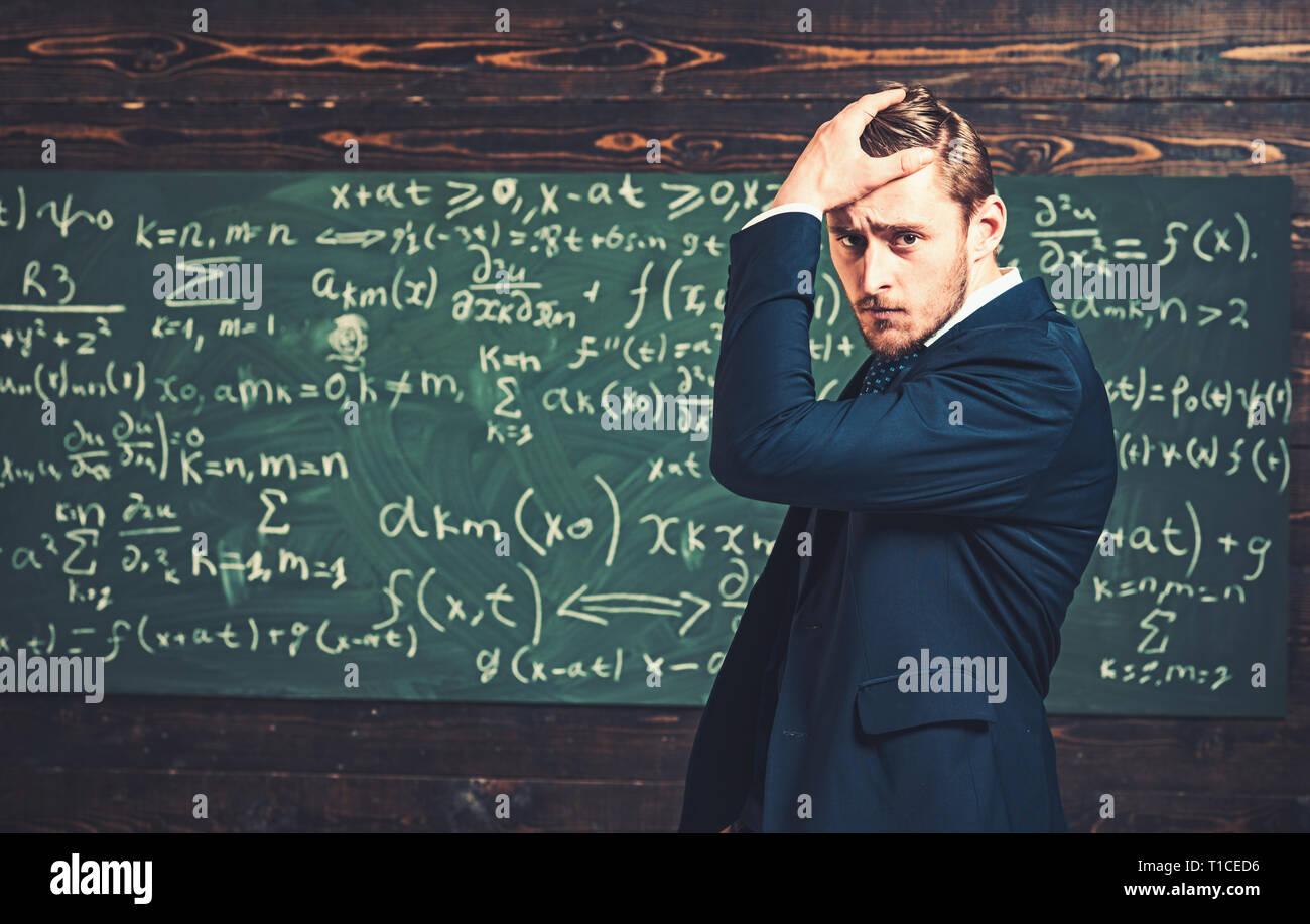 Thoughtful young man in elegant suit standing over green board full of writing. Anxious intelligent professor holding his hand on head - Stock Image