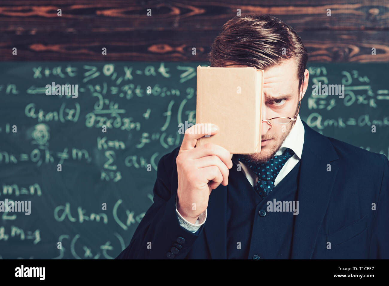 Young man in suit covering his face with book. Closeup portrait of young blond aristocrat with stylish hair and beard - Stock Image