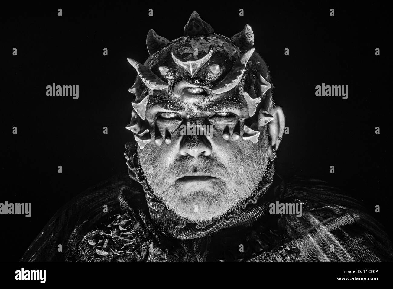 Alien, demon, sorcerer makeup. Horror and fantasy concept. Man with third eye, thorns or warts. Demon on black background, close up. Senior man with - Stock Image
