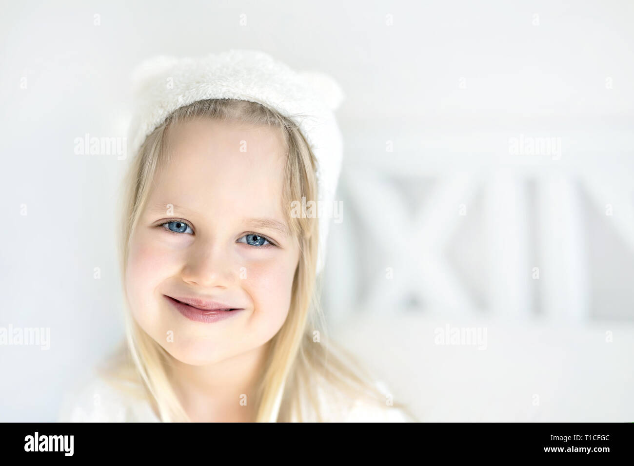 Portrait cute blond preschooler girl. Smilling kid in white hat. Child on bed in nursery room. Adorable baby wearing funny hat with small ears. Happy  - Stock Image