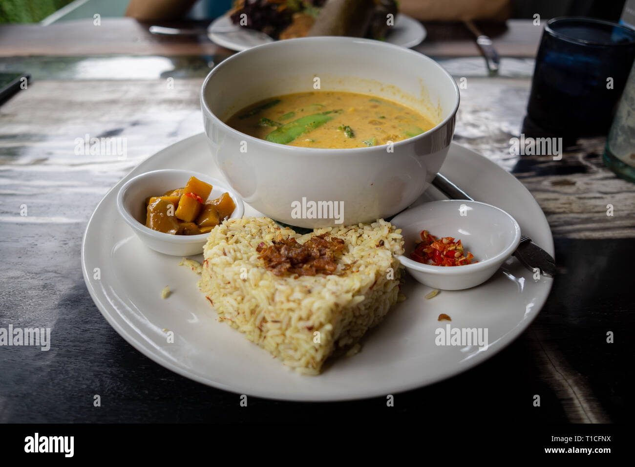 Delicious rice and a bowl of soup with spicy sauce make this lunch very tasty and delicious. It is organic and healthy too - Stock Image