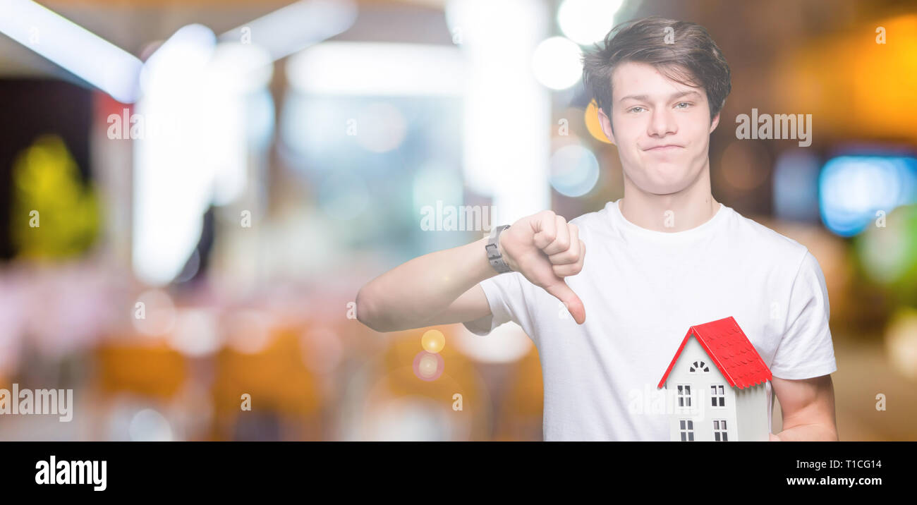 Young man holding house over isolated background with angry face, negative sign showing dislike with thumbs down, rejection concept - Stock Image