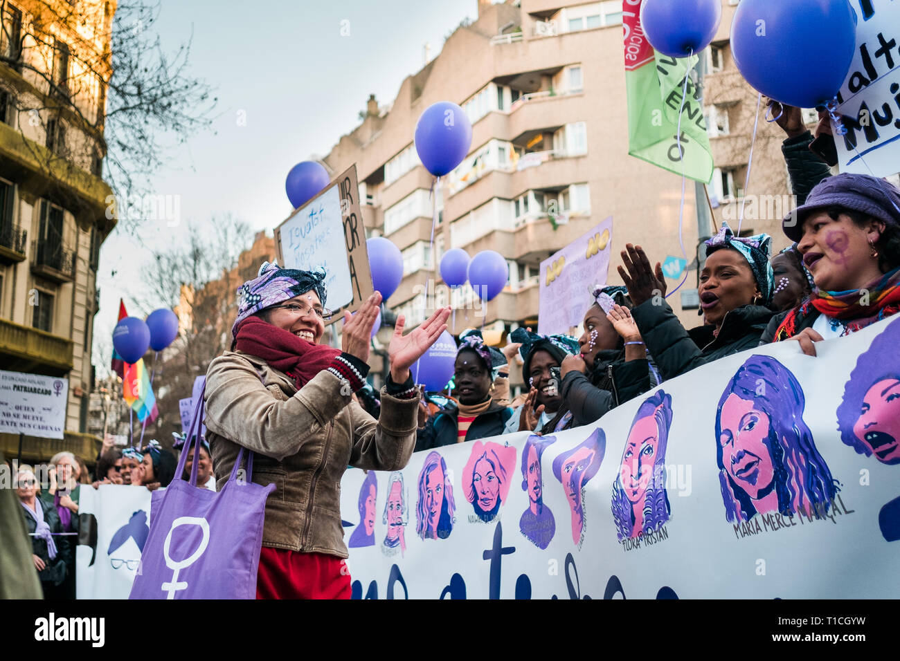 Barcelona, Spain - 8 march 2019:  women chanting and calpping in the city during woman's day with purple balloons - Stock Image