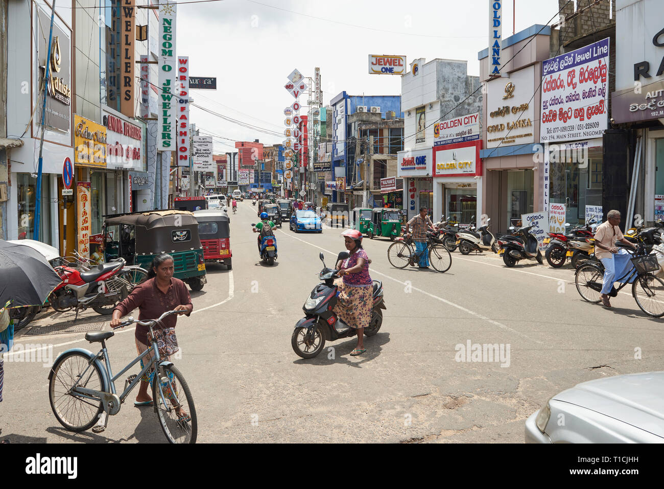 Busy commercial road in Negombo, Sri Lanka, on a sunny day, with heavy traffic of bicycles, cars, motorbikes and tuk-tuks. Stock Photo