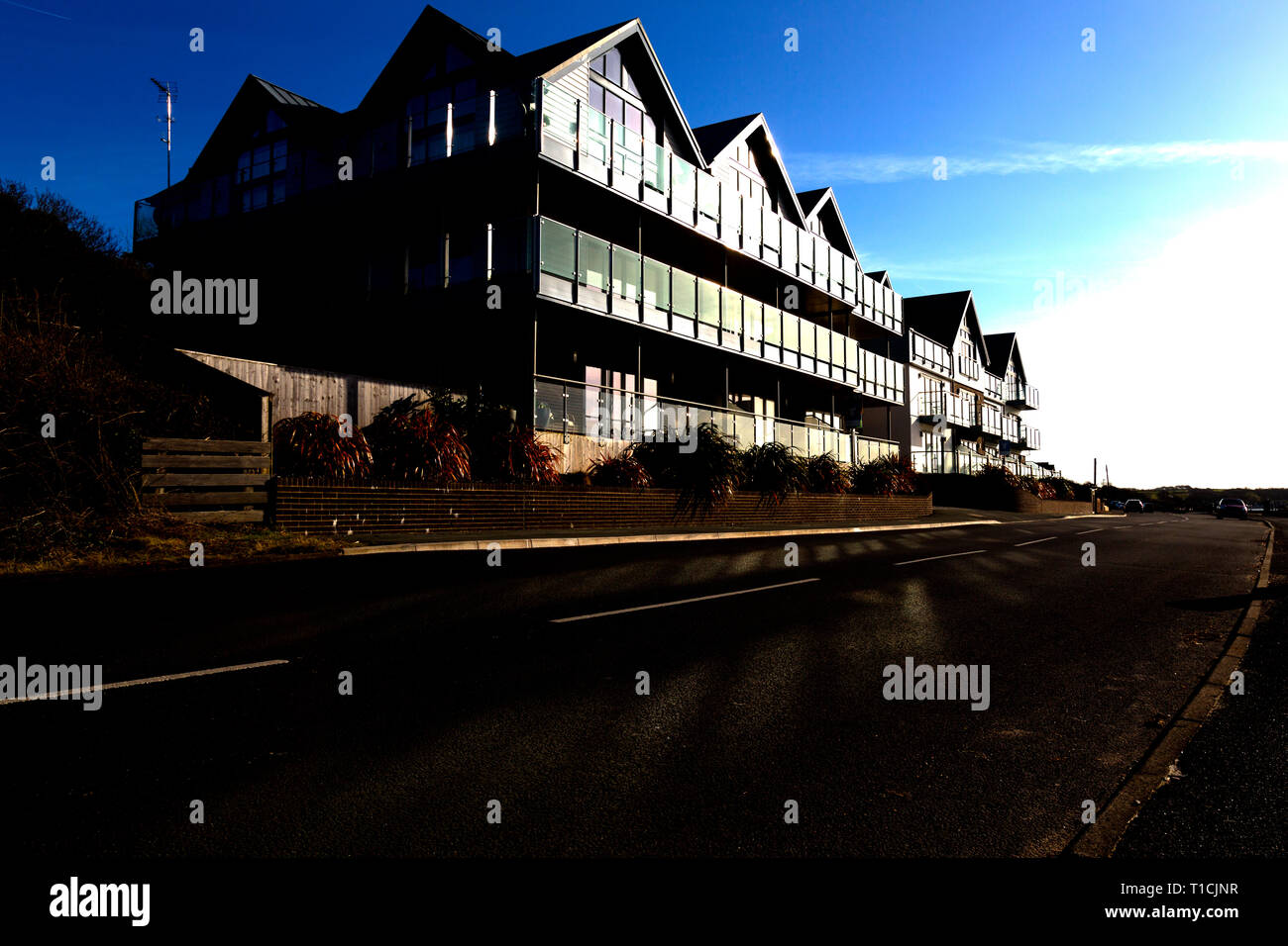 Modern,seaside,house,development,glass,balconies,balcony,sun,reflected off,energy,saving,windows.glass,solar,power,panels,Gurnard,Isle of Wight,UK - Stock Image