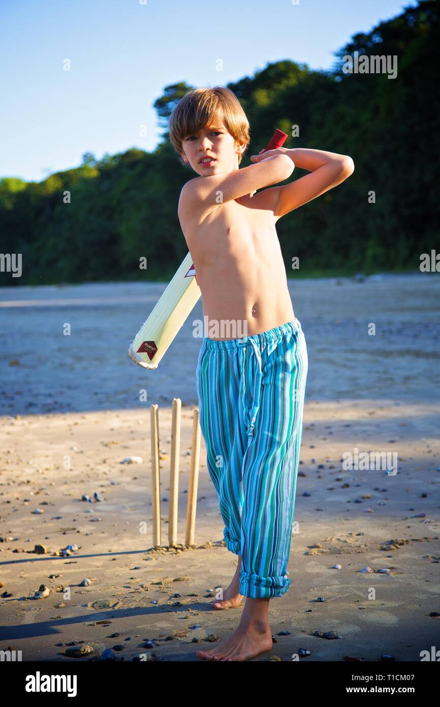 Handsome young 8-10 year old boy having fun playing cricket with bat on the beach - Stock Image