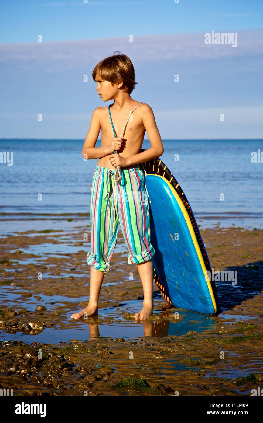 Handsome young 8-10 year old boy pulling a bodyboard at the beach - Stock Image