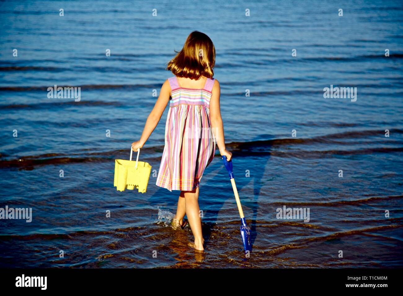 Back view of pretty young girl with blonde hair in sundress with bucket and spade paddling - Stock Image