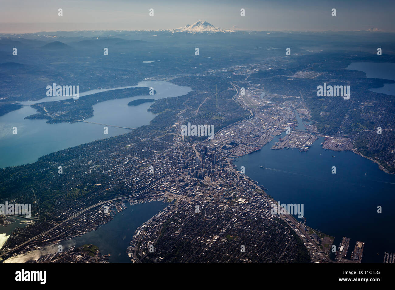 Aerial view of Seattle urban sprawl and bays with snow capped mountain in the distance - Stock Image