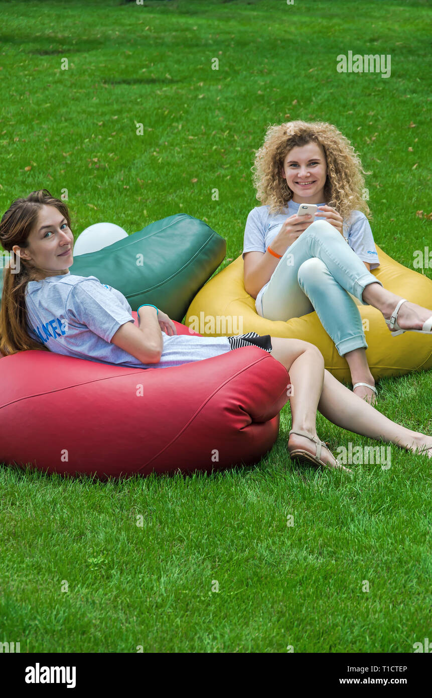 Dnipro, Ukraine - June 27, 2018: Girls volunteers resting on a bean bag chair in a city park on a green lawn - Stock Image
