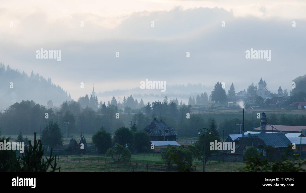 Foggy morning panorama of green mountain valley, Transcarpathian, Vatra Dornei, Bucovina Region, Europe. Beauty of nature concept background. - Stock Image